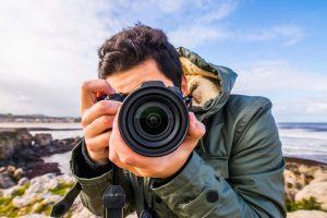 Urlaubsfotos Tipps: Mann fotografiert mit einer Spiegelreflex-Kamera