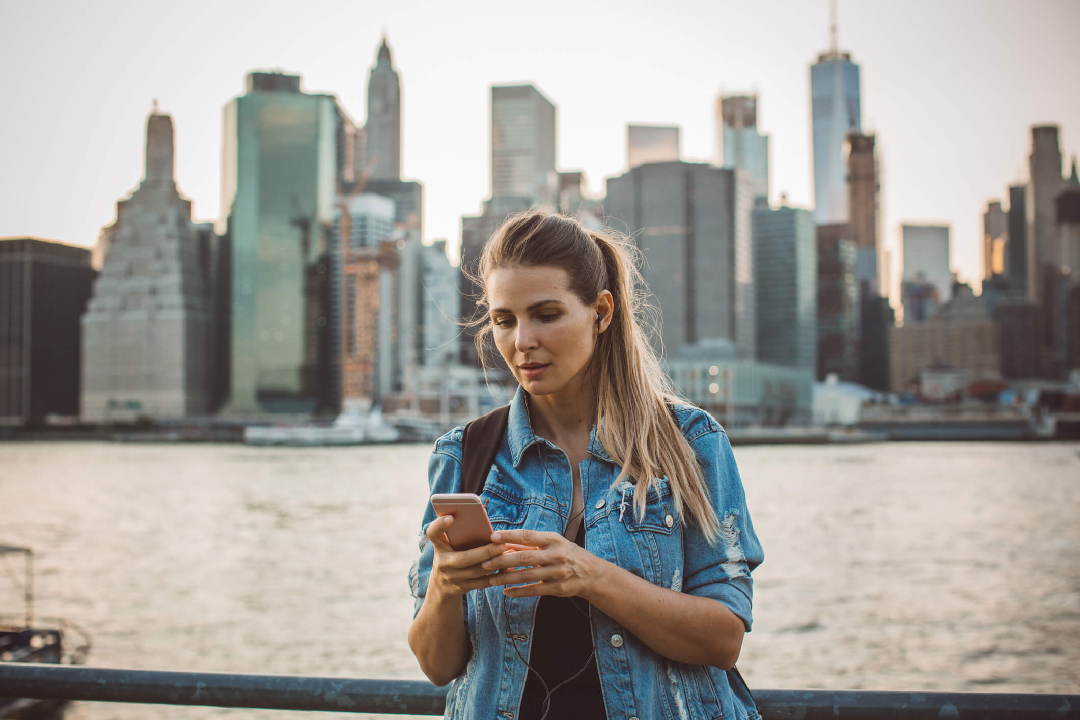 SIM-Karte USA: Eine junge Frau mit Smartphone vor der Skyline Mannhattens