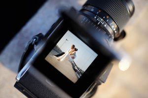 Auf Hochzeiten fotografieren: Brautpaar im Vorschaufenster einer Kamera