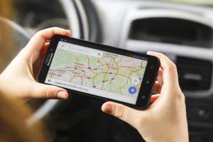 Google-Maps-Alternative: Frau mit Smartphone am Steuer